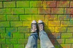 Pieds dans la vue supérieure d'espadrille de jaeans sur le fond de holi Photographie stock libre de droits