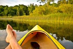 Pieds dans le bateau sur le lac Images stock