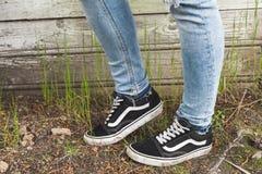 Pieds dans les blues-jean et des espadrilles noires Photo stock