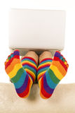 Pieds dans les chaussettes colorées sous l'ordinateur portable Photographie stock