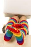 Pieds dans les chaussettes colorées sous l'ordinateur portable croisé Photographie stock libre de droits