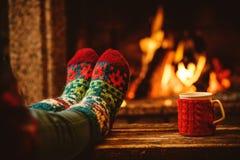 Pieds dans les chaussettes de laine par la cheminée de Noël détend le femme images stock