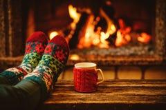 Pieds dans les chaussettes de laine par la cheminée de Noël détend le femme Photos stock