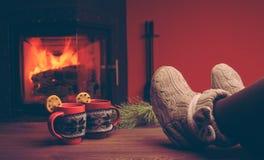 Pieds dans les chaussettes de laine par la cheminée de Noël détend le femme Image libre de droits