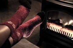 Pieds dans les chaussettes de laine rouges de Noël par la cheminée Photos libres de droits