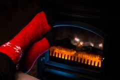 Pieds dans les chaussettes de laine rouges par la cheminée Photographie stock