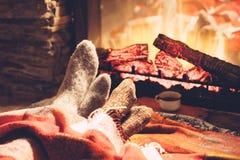 Pieds dans les chaussettes par le feu Photographie stock
