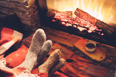 Pieds dans les chaussettes par le feu Images stock
