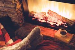 Pieds dans les chaussettes par le feu Photos stock