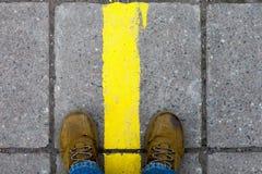 Pieds dans les chaussures jaunes sur le trottoir Images stock