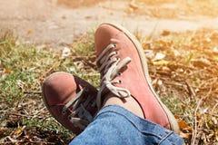 Pieds dans les espadrilles et des jeans rouges dehors Images stock