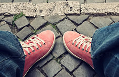 Pieds dans les espadrilles et des jeans rouges dehors Photos libres de droits