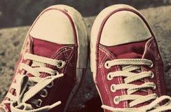 Pieds dans les espadrilles et des jeans rouges sales dehors Photo stock
