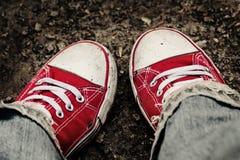 Pieds dans les espadrilles et des jeans rouges sales dehors Photo libre de droits