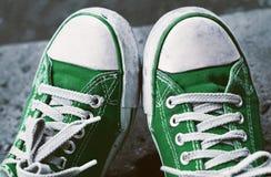 Pieds dans les espadrilles et des jeans verts sales dehors Photos libres de droits