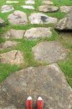 Pieds dans les espadrilles rouges et le passage couvert en pierre Photos stock