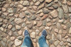 Pieds dans les jeans et des espadrilles sur le trottoir en pierre Images stock