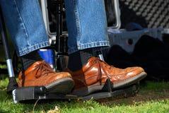 Pieds dans un fauteuil roulant Photo stock