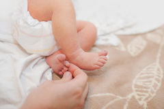 Pieds de bébé évasés dans de belles mains de mères avec le foyer mou sur le pied du ` s de babie Photographie stock