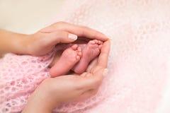 Pieds de bébé évasés dans des mains de mères Photos libres de droits