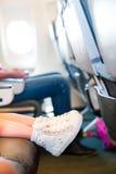 Pieds de bébé dans des espadrilles sur le siège dans les avions Image libre de droits