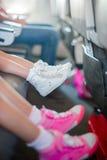 Pieds de bébé dans des espadrilles sur le siège dans les petites filles adorables d'avions marchant dehors dans le domaine de fle Photos libres de droits