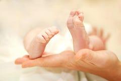 Pieds de bébé dans des mains de la mère. Photo libre de droits