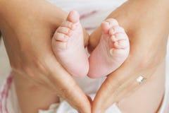 Pieds de bébé dans des mains de mère - forme de foyer images stock