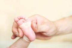 Pieds de bébé dans le dad& x27 ; main de s avec un fond brouillé Images libres de droits