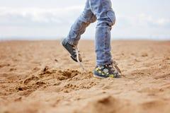 Pieds de bébé dans les jeans et des espadrilles fonctionnant sur le sable pendant l'été Photos libres de droits