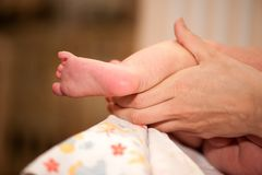 Pieds de bébé dans les mains de la mère sur la table changeante photo stock
