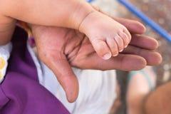 Pieds de bébé dans sa paume de père Photo stock