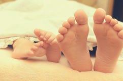 Pieds de bébé de dessous la couverture sur le lit Image stock