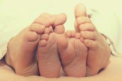 Pieds de bébé de dessous la couverture sur le lit Photos libres de droits
