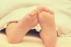 Pieds de bébé de dessous la couverture sur le lit Images libres de droits