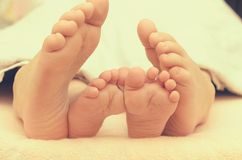 Pieds de bébé de dessous la couverture sur le lit Photo stock