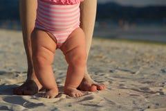 Pieds de bébé et de parent sur la plage de sable Image libre de droits
