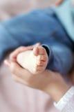 Pieds de bébé nouveau-né sur la paume du ` s de mère Photo stock