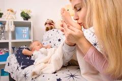 Pieds de baiser de bébé de jeune mère Enfance heureux, famille d'amour photographie stock
