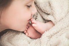 Pieds de baiser de grande soeur de son frère nouveau-né Photographie stock