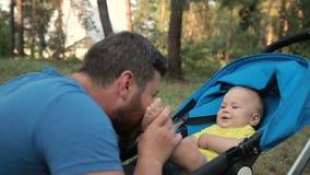 Pieds de baiser de père affectueux de son fils de bébé en parc banque de vidéos