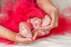 Pieds de chéri dans des mains de mère Photographie stock libre de droits