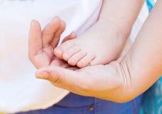 Pieds de chéri dans la main de mère Photos stock
