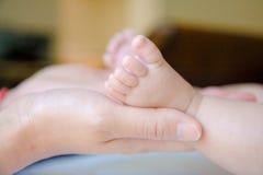 Pieds de chéri et mains de la maman Image libre de droits