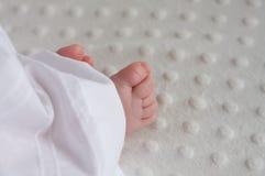 Pieds de chéris collant hors d'un équipement de baptême Photographie stock libre de droits