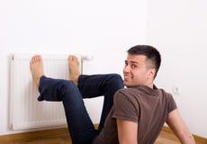 Pieds de chauffage d'homme sur le radiateur Photographie stock