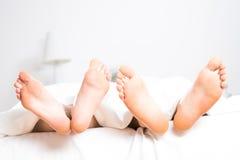 Pieds de couples dans le lit Image stock