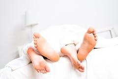 Pieds de couples dans le lit Photographie stock