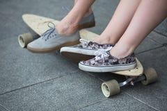Pieds de couples des adolescents dans des espadrilles sur le longboard Images stock