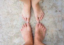 Pieds de couples sur la fin concrète de la terre  Photographie stock